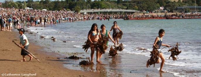 Local children make seaweed costumes while crowds gather to watch the wakas gather off Te Beach © Catherine Langford